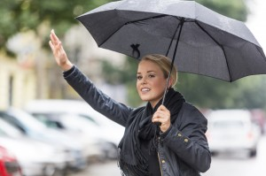 Calling a cab with umbrella